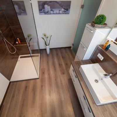 Bad-Referenzbad-Wöhlfühlbad-in-nussbraun-Waschtisch-Armatur-bodengleiche-Dusche