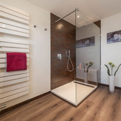 Bad-Referenzbad-Wöhlfühlbad-in-nussbraun-bodengleiche-Dusche-Badheizkörper