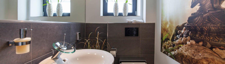 Bad-Referenzbad-buddha-begrüsst-sie-Waschtisch-Armatur-Dusch-WC
