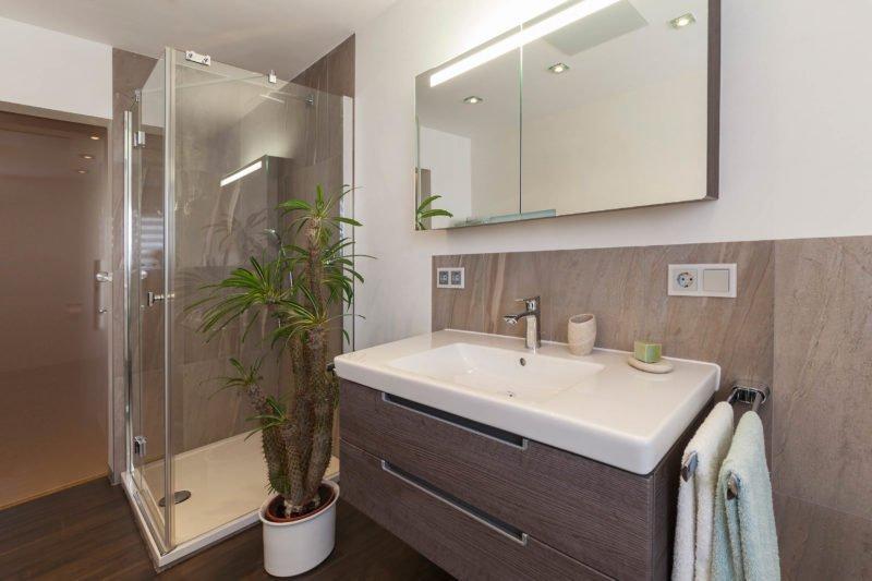 Bad-Referenzbad-marmor-und-holz-bodengleiche-Dusche-beleuchteter-Spiegelschrank-Armatur